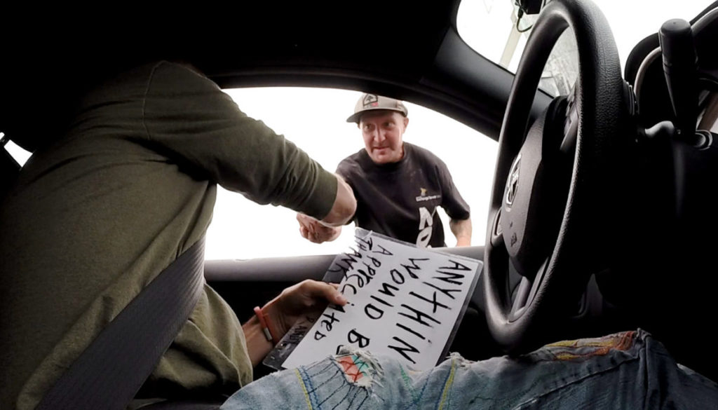 SIGNS OF HUMANITY Willie Baronet buys a sign from Randy in Portland